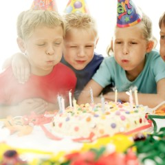 Two Boys and a Girl (8-12) Blowing Out Candles on a Birthday Cake