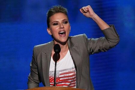 Scarlett Johanssen raising her arm in a speech in protest